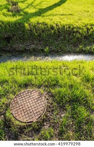 old rusty the sewer hatch with cover and a gutter with water and ooze is in the park among fresh spring grass - stock photo