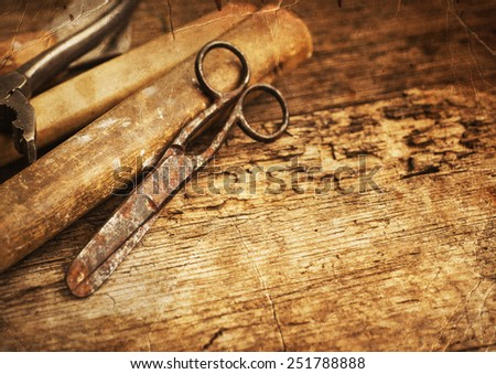 Old rusty tools, scissors, hummer on old wooden table background - stock photo
