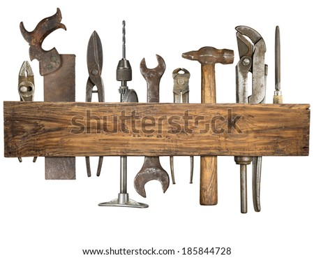 Old rusty tools under wooden plank. - stock photo
