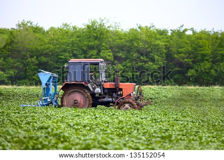 Old, rusty, tractor on an agricultural field