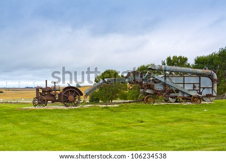 Old rusty tractor with wind turbines in the background. - stock photo
