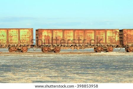 Old rusty train cars with stalactites of salt in the lake Baskunchak - stock photo