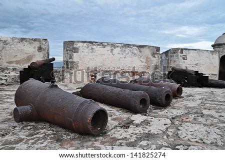 Old Rusty Unused Guns over the Rooftop in Cuba - stock photo