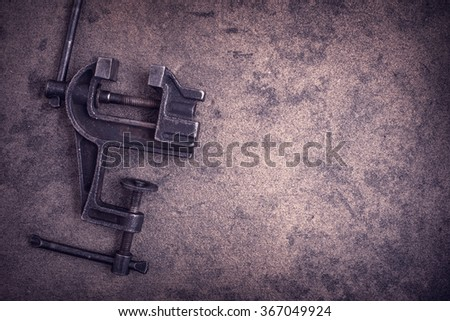 Old rusty vise tool on grunge metal surface with copy space.Toned - stock photo