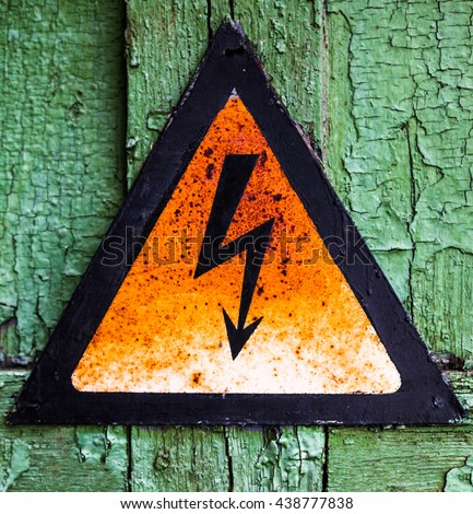 Old rusty warning high voltage sign on cracked green wooden surface - stock photo