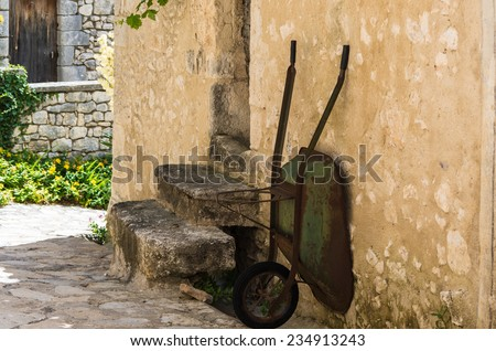 Old rusty wheelbarrow is positioned against a stone house in France.