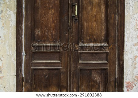 Old rusty wooden door on a backdrop of a old abandoned wall - stock photo