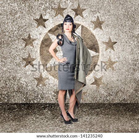 Old 50s photo of an Asian military pinup girl standing in a full body pose wearing army issued flight cap and goggles on retro air force background - stock photo