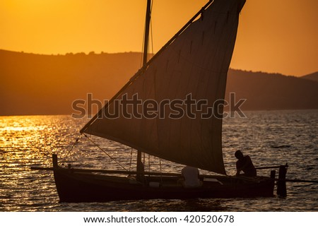 Old sailing boat on the sunset - stock photo
