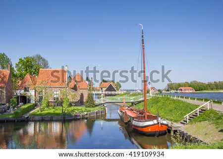 Old sailing ship in a canal in Enkhuizen, Netherlands - stock photo
