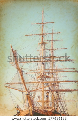 Old sailing ship on paper texture. Ancient sailboat on grunge background. Exterior of the old tall ship. Historic three-masted sailing ship. Vintage postcards with sailboat in retro style. - stock photo