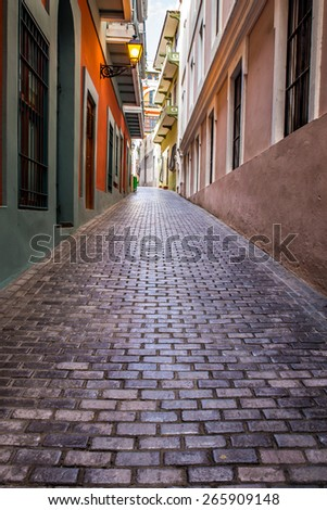 OLD SAN JUAN, PUERTO RICO - MARCH 29, 2015:  Cobblestone street scene with colorful buildings in Old San Juan, Puerto Rico.  - stock photo