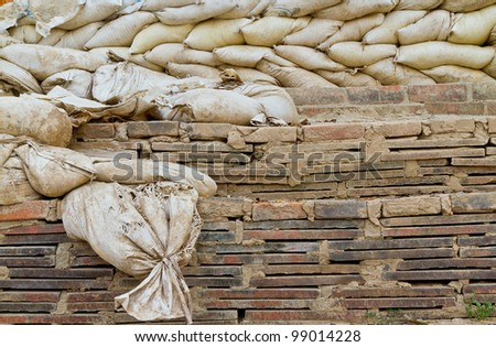 old sand bags on brick wall - stock photo