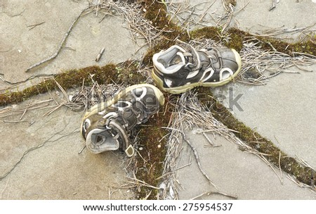 Old sandals baby on a background of stones