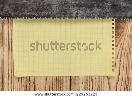 old saw and a piece of notebook on wooden background