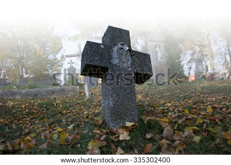 Old scary graves in the cemetery. Spooky tomb stones in a foggy autumn scene in the graveyard. All Saints Day / All Hallows / 1st November. Slovakia - stock photo