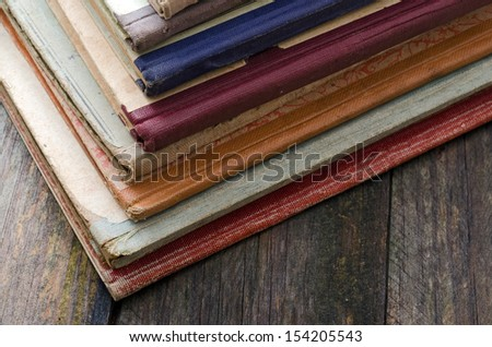 old school books stacked on a wooden table