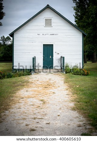 Old school house at the end of a gravel path.