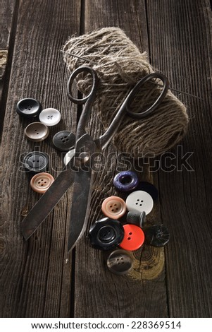 Old scissors and buttons on the wooden table  - stock photo