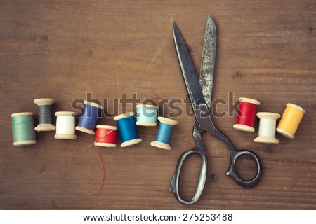 Old scissors and wooden spools of colored thread lie on a wooden table - stock photo