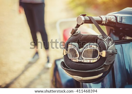 Old scooter with retro helmet on seat - stock photo