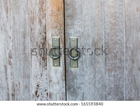 Old scratched door and two ring handle. - stock photo