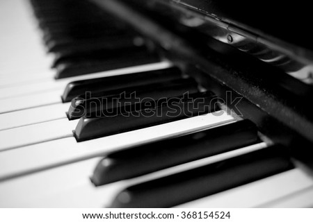Old scratched dusty piano close up. Black and white image with selective focus - stock photo