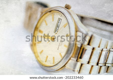 Old scratched wristwatch with metal wristlet - stock photo