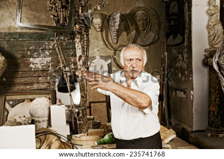Old sculptor tells emotional story at his workshop - stock photo