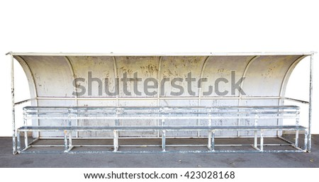 Old  seats on outdoor stadium players bench, chairs with worn paint below white roof. Autumn leaves, end of football season. - stock photo