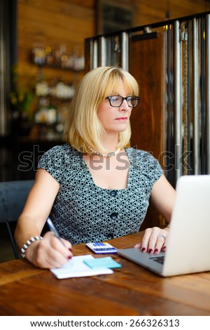 Old senior blonde business woman in the glasses sitting at a cafe city with a laptop and calculator, writes notes