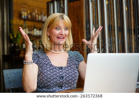 Old senior blonde business woman 60-65 years, alone with laptop in summer cafe with surprise and gesture on his face  - stock photo