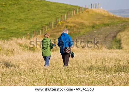 Old senior citizen couple taking a walk in the field in Ireland - stock photo