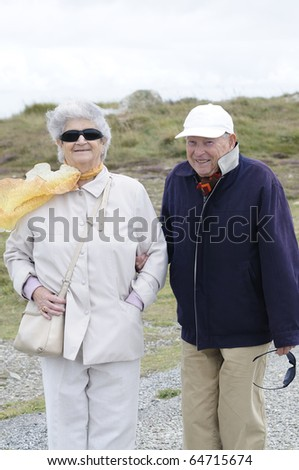 Old senior couple walking along the coast holding their hands and smiling. - stock photo