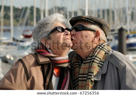 Old senior man kissing his wife at the yacht harbor. - stock photo