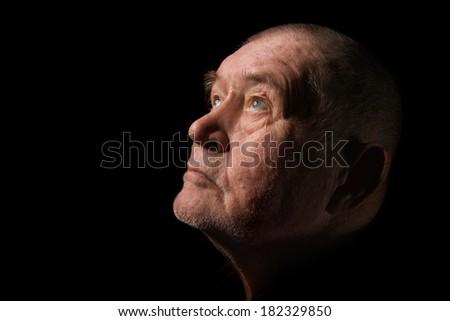 old senior man looking up praying in dark - stock photo