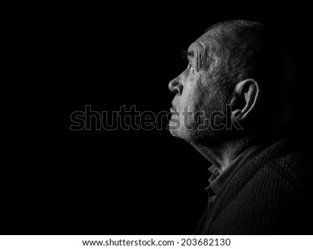 old senior man looking up praying in dark monochrome image