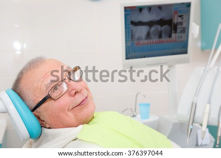 Old senior man with glasses sitting in a dental chair in a dentist's office. Monitor with X-ray on background - stock photo