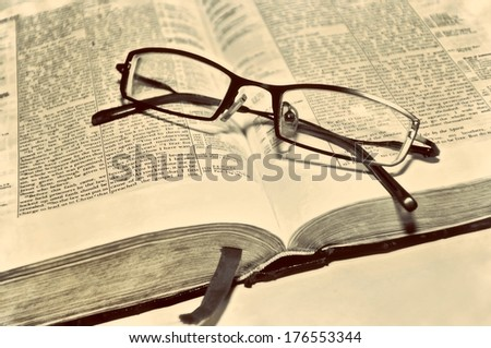 Old sepia antique retro vintage book Bible Scriptures and glasses Christian - stock photo