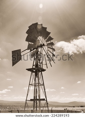 Old sepia photo of a windmill on a farm. Image is shot into the sun