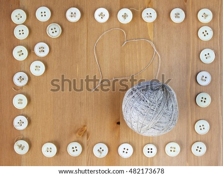 Old sewing buttons frame and ball of linen threads in the middle. Flat lay, top view. Copy space