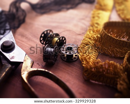 old sewing machine bobbins and fringe or lace tapes and silk trimmings with gold (brass) scissors on a old grungy work table. Intentionally shot in retro low key tone and shallow depth of field. - stock photo