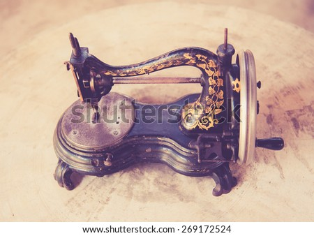 old sewing machine on a table,vintage color toned image - stock photo