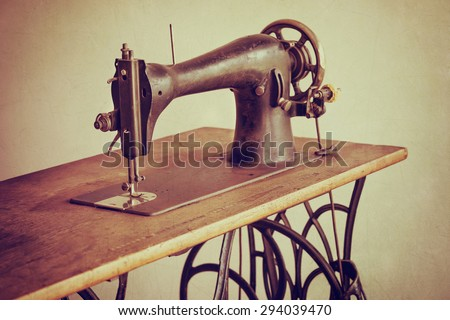 Old sewing machine on textured vintage background - stock photo
