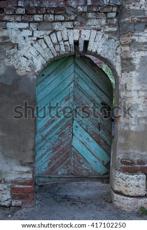 Old shabby wooden turquoise door in ancient brick arch - stock photo