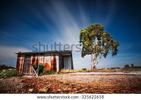 Old shack made of sheet metal next to a tree with a long exposure - stock photo