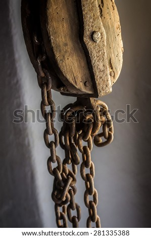 Old Sheave with hanging rusty chains - stock photo