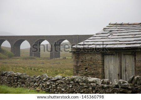 Old shed and viaduct Yorkshire Dales Yorkshire England - stock photo