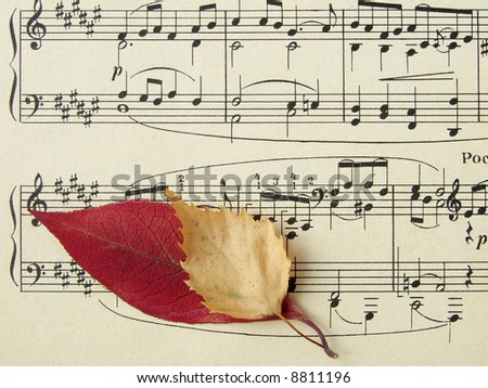 old sheet of musical symbols with colorful autumnal leaves