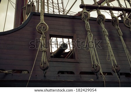 Old ship, gun in sailboat. Vintage retro style.